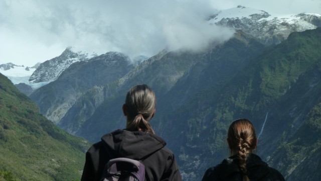 back of tourists heads looking at franz josef glacier