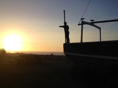 daniel on a boat at hokitika beach at sunset
