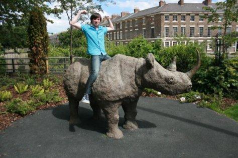 daniel sitting on a rhino outside hancock museum newcastle