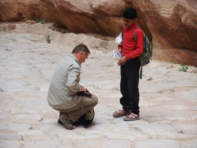 tourist buying postcards from boy in petra